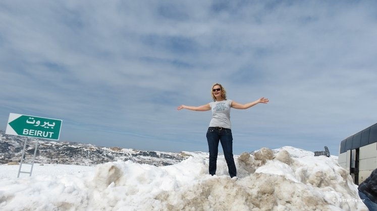Woman standing in her T-shirt on top of snow in the mountains of Beirut Lebanon
