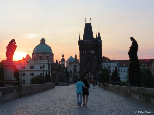 Couple takes a romantic morning walk over the Charles Bridge