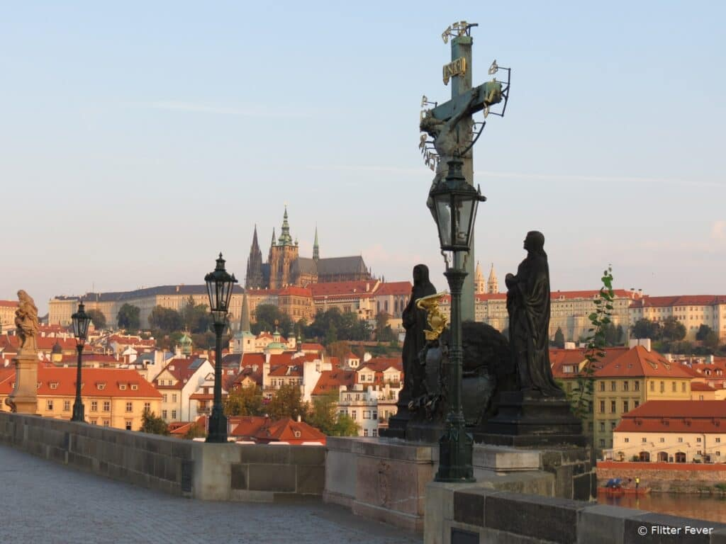 Jesus status on the Charles Bridge with Prague Castle on the background