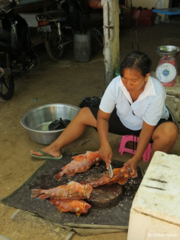 Balinese woman cleaning fresh caught fish