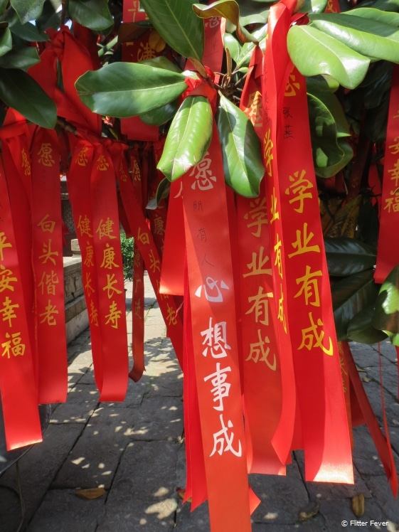 Red satin ribbons with good wishes on a tree in City God Temple, Zhujiajiao, China