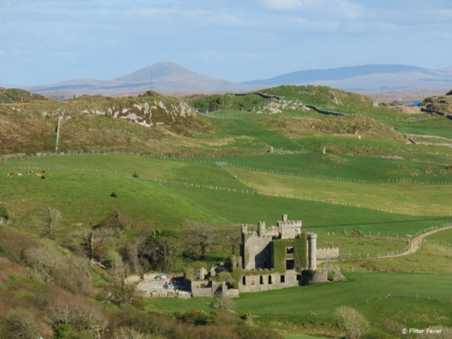 Old castle in the middle of all the green landscape at The Loop in Connemara