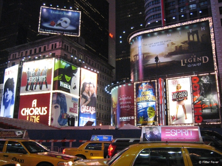 Taxis and billboards at Times Square at night NYC