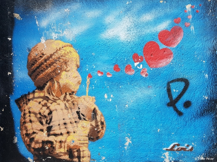 Banksy style kid blowing heart bubble blower street art Lisbon