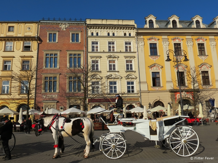 Horse and carriage in front of colorful houses at Rynek Główny Krakow