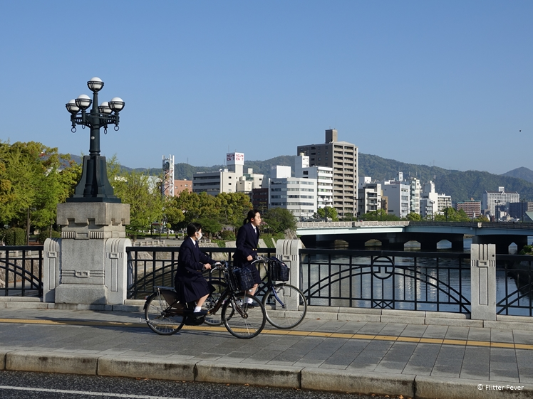 Uniformed Japanese school girls cycling over a bridge across the Motoyasu River in Hiroshima