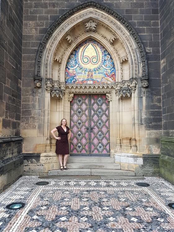 Woman in dress standing in front of big church door in Prague