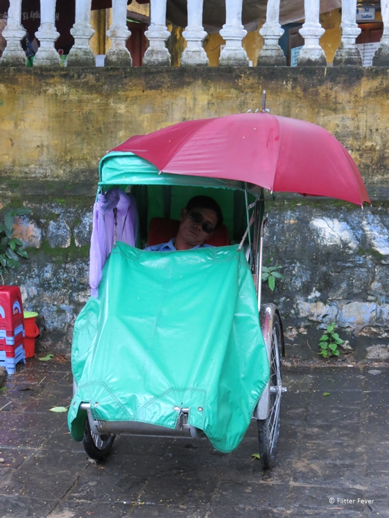 Cyclo driver takes a nap in rainy Hoi An Vietnam