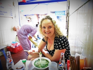 Eating Pho Ga in a local street food place in the Old Quarter