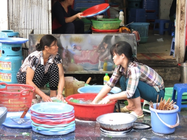 Ladies doing the dishes on the street (Hanoi)