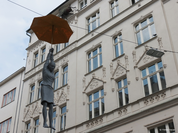 Lady hanging on wire with umbrella Prague New Town