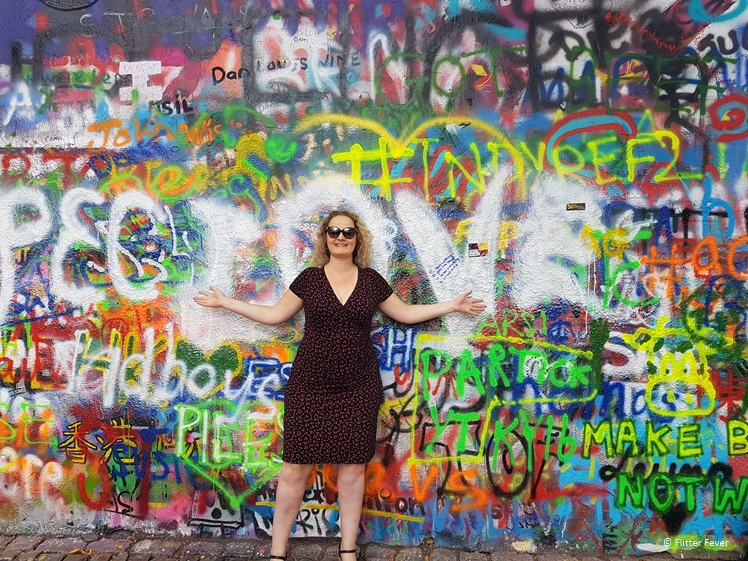 Woman in dress in front of graffiti wall in Prague