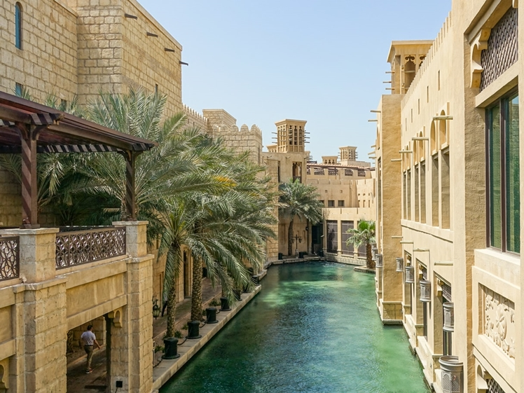 beige arab buildings with river and palmtrees in Dubai