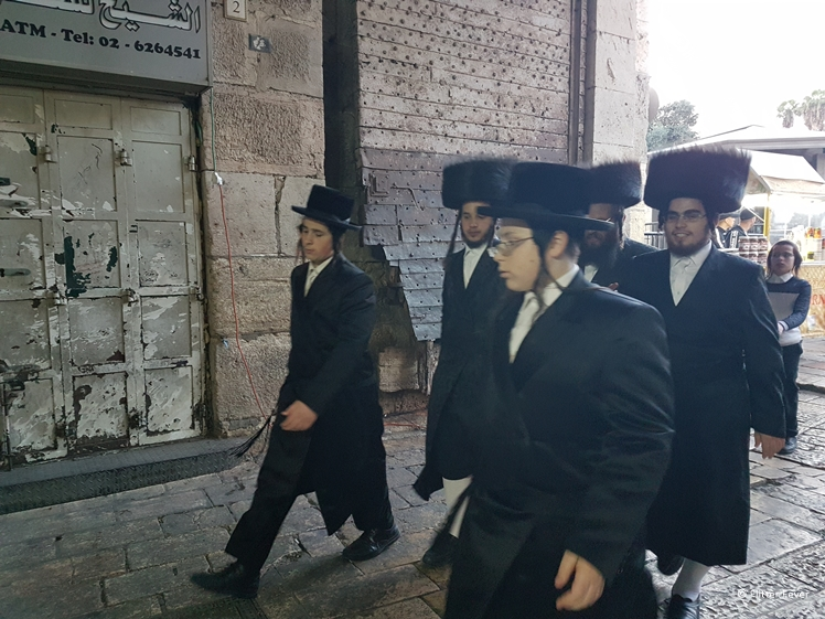 Jewish Orthodox men walking inside Damascus Gate on their way to Western Wall for Shabbat prayers