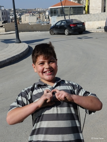 Palestinian kiddo showing sign of love Bethlehem