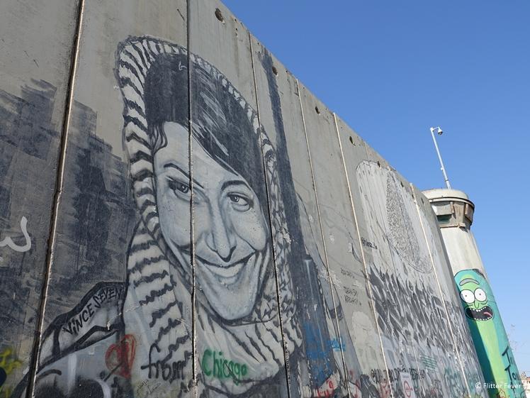 Palestinian woman street art at watch tower Israeli West Bank Barrier Bethlehem