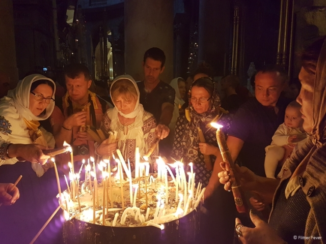 People lighting candles at the Church of the Holy Sepulchre Jerusalem