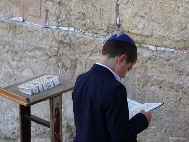 Young boy reading the Torah at the Wailing Wall
