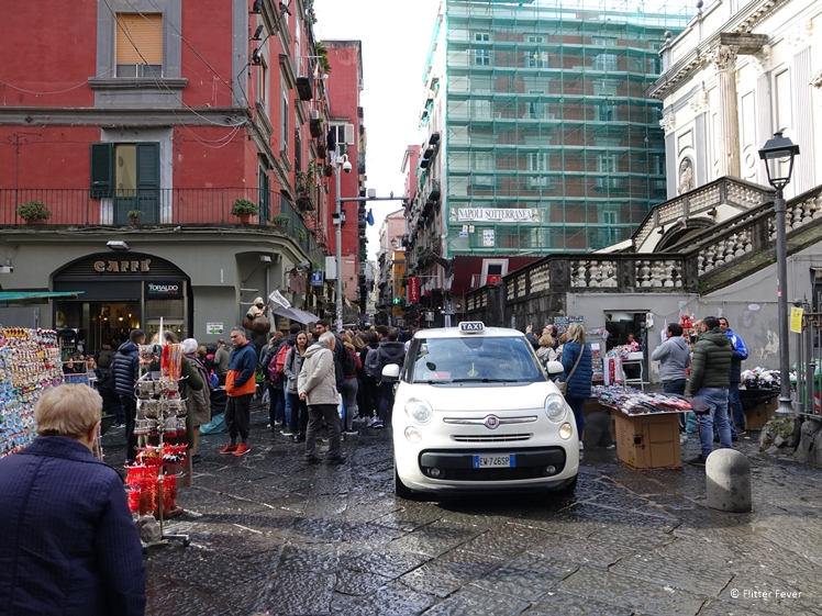 Taxi driver rushes through the crowd in the centre of Naples