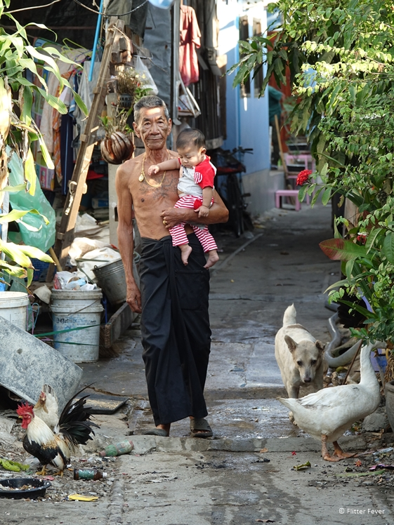 Grandpa with grandchild in his arms, goose, chickens and dog in slum of Bangkok