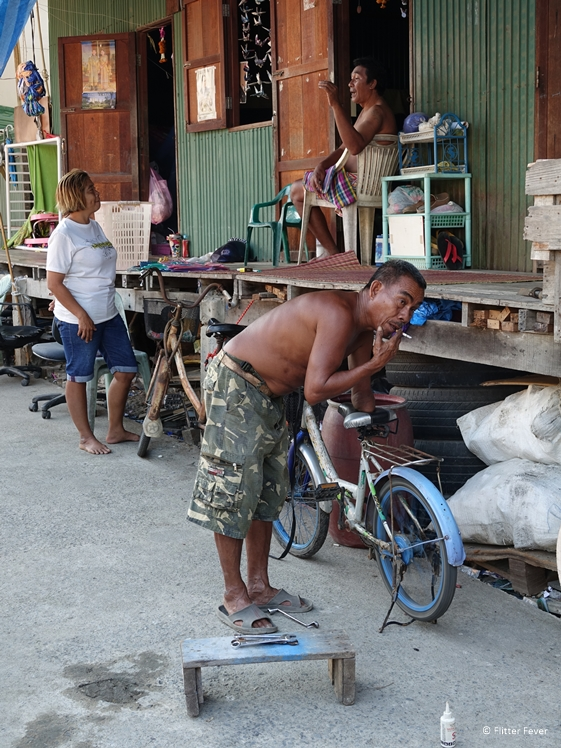 Father fixing bicycle and man and woman on background in slum of Bangkok