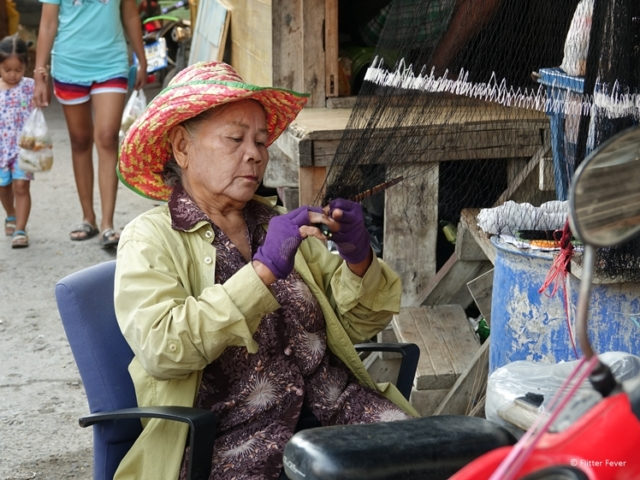 Older woman fixing fishing net at slum in Bangkok