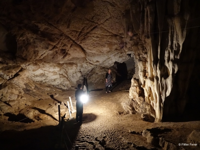 Tham Lod cave with guide and his lamp