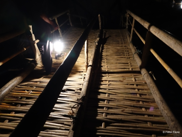 The local guide leads us over the bamboo bridge in Lod Cave