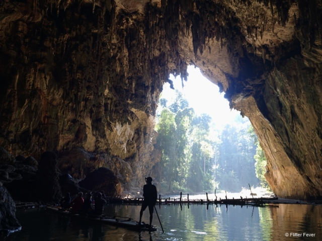 The spectacular gap view of the jungle outdoors seen from the river inside Lod Cave
