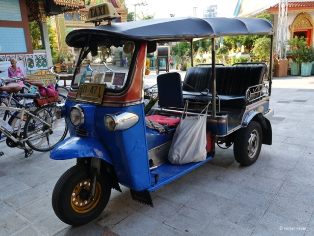 Tuktuk taxi parked at temple with kindergarden in Bangkok