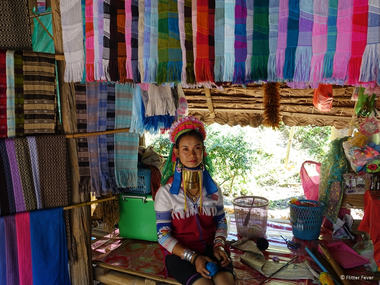 Karen tribe Long Neck giraffe lady sitting between the scarves she has woven in Pai