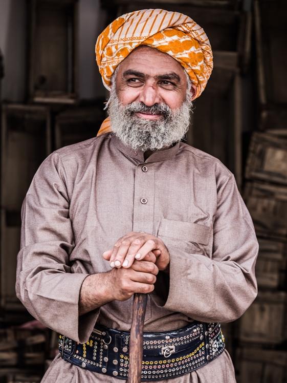 Man standing while holding brown wooden walking cane in Aljanadriah