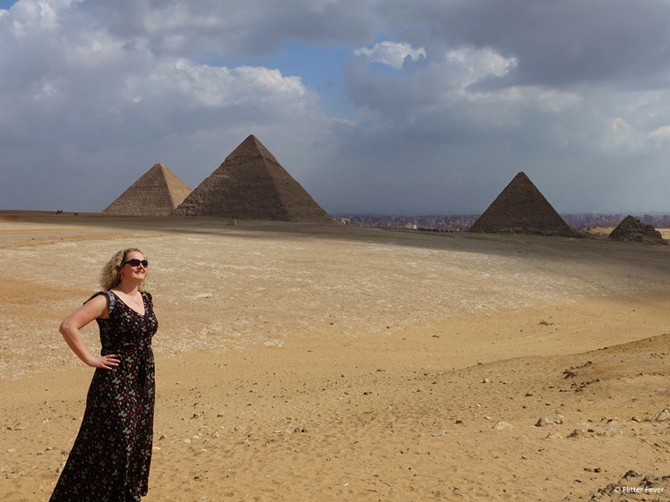 Woman in dress standing in front of the Giza pyramids in Egypt