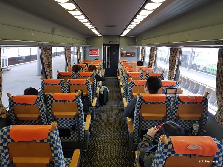 Orange themed train interior to Huis ten Bosch