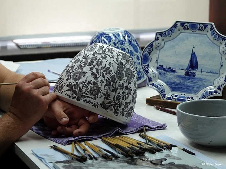 A bowl gets painted at Royal Delft - the blue color appears after baking