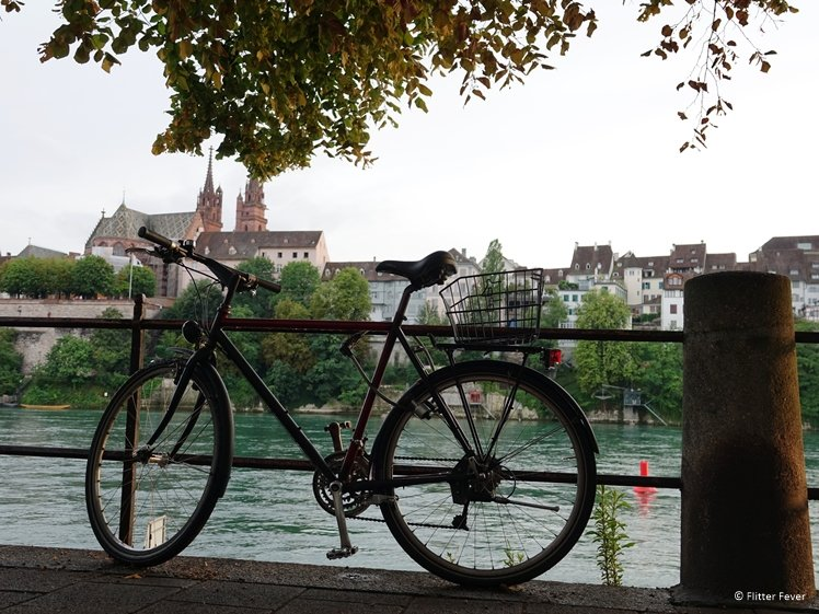 Parked bicycle at the Rhine River in Basel with Munster on the background