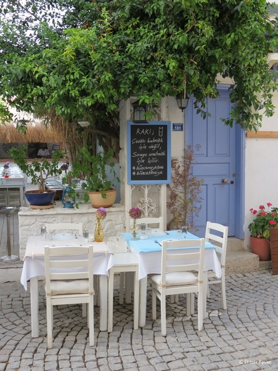 Cute restaurant seating at lavender colored door