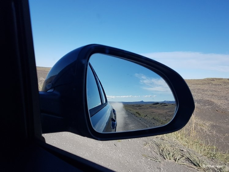 Side mirror of car with dust behind due to gravel road 864