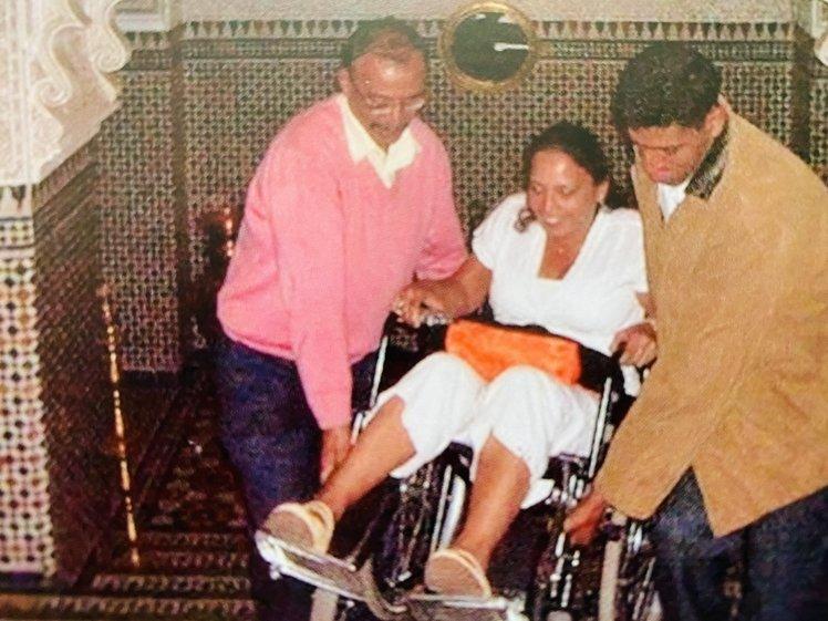 Vrouw in rolstoel gedragen door twee mannen in Marrakech