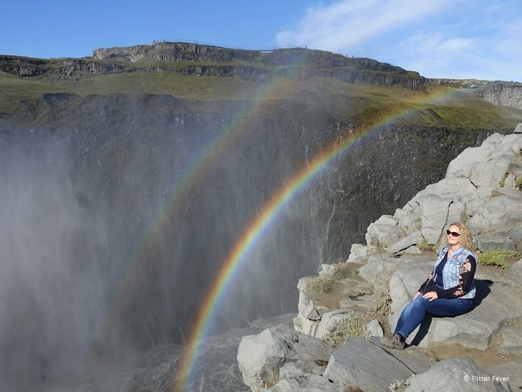 Woman sitting on rocks with double rainbow in front of Dettifoss waterfall Iceland