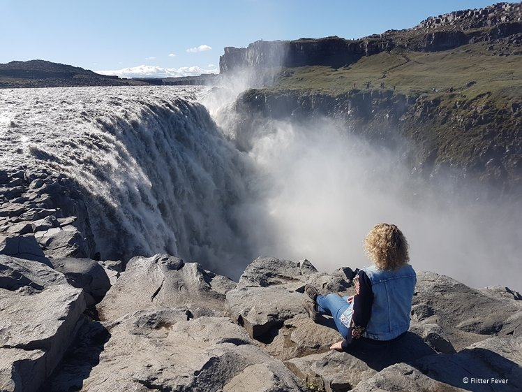 Woman sitting in front of watching waterfall dettifoss on Iceland