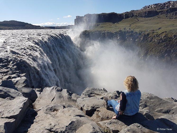 Vrouw zit te kijken naar het krachtige water van de Dettifoss waterval in noord IJsland