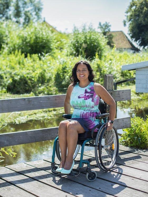 Mooie vrouw met jurk in rolstoel in park op zonnige dag