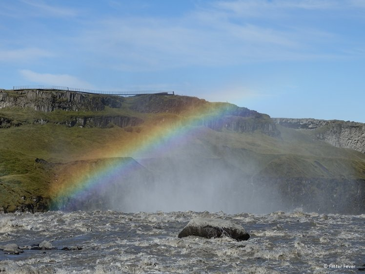 Rainbow above Dettifoss waterfall from behind