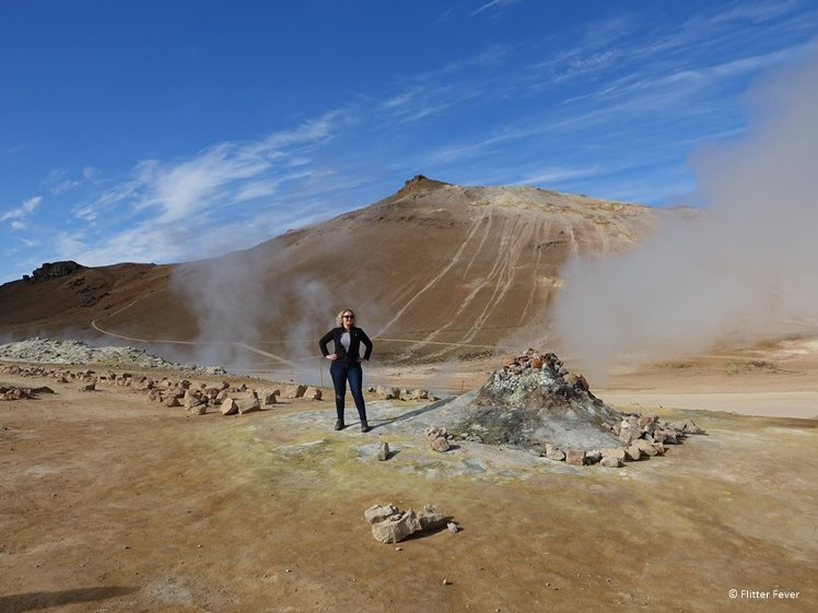 Lady standing next to smoking fumaroles produced by georthermal activity at Hverir