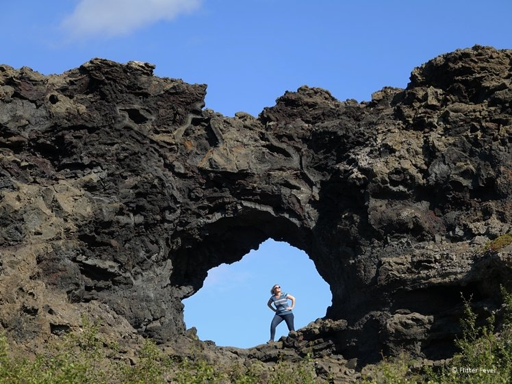 Woman standing in hole formed by lava rocks