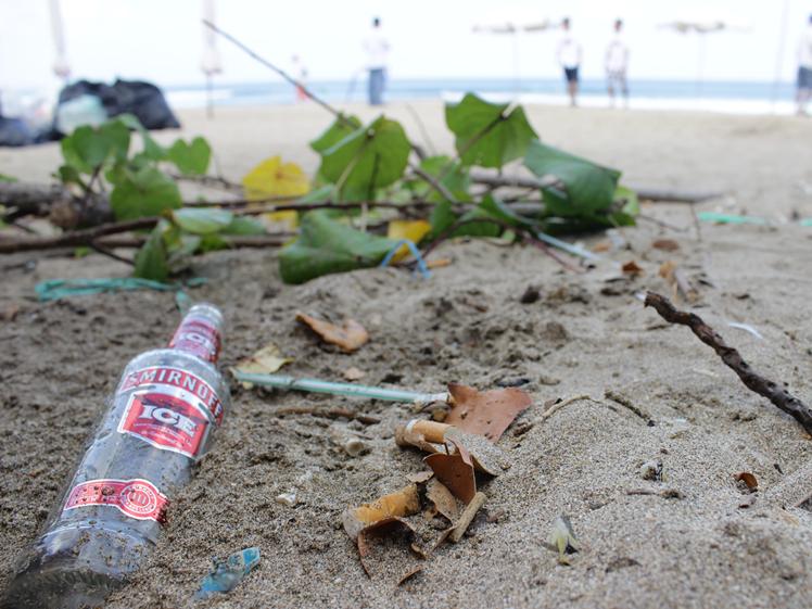 Vodka bottle and plastic waste on Kuta Beach