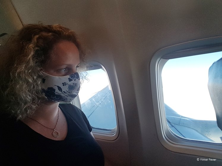 Woman wearing Delft Blue facemask during flight