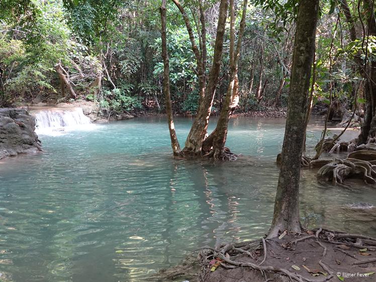 Trees and crystal clear water at Huay Mae Khamin Waterfalls