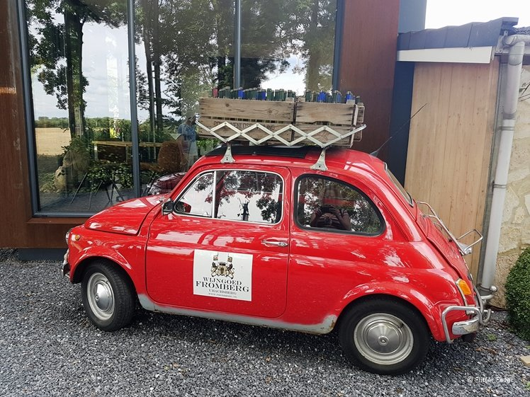 Cute little red Fiat car with wine bottles on top at Fromberg Winery